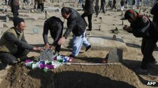 Afghan men pray over the grave of a victim of Tuesday's bomb attacks, apparently targeting Shia Muslims, at the Kart-E Sakhi cemetery in Kabul on Wednesday