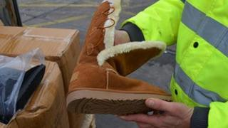 A UKBA officer with one of the fake Ugg boots seized at Southampton Docks