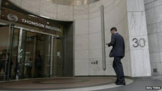 A man enters the Thomson Reuters building at Canary Wharf, London