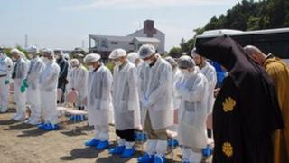 Residents of Tomioka in white protection suits evacuated to the city of Koriyama