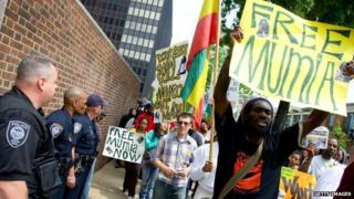 Protesters hold signs in support of Mumia Abu Jamal while police officers look on