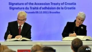 Croatian President Ivo Josipovic (left) and Prime Minister Jadranka Kosor sign their country's accession treaty in Brussels, 9 December