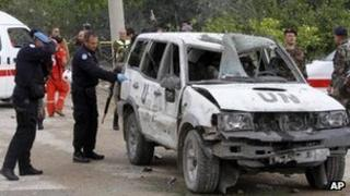UN personnel inspect the vehicle damaged in the bombing outside Tyre (9 December 2011)