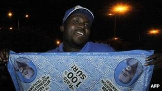 A Congolese man holds a cloth printed with pictures of DR Congo incumbent president Joseph Kabila on December 8, 2011