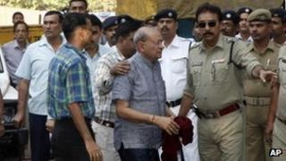 R.S. Agarwal, centre right wearing glasses, one of the main accused in the Amri hospital fire, and other accused are brought to a court in Calcutta, India, on 10 December