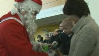 A child receives a toy from Father Christmas at the John Radcliffe Hospital