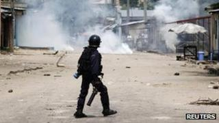 A riot policeman faces opposition protesters through a could of tear gas in Democratic Republic of Congo's capital Kinshasa on 10 December