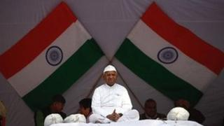 Veteran Indian social activist Anna Hazare sit in front of India's national flags during his day-long fast in Delhi