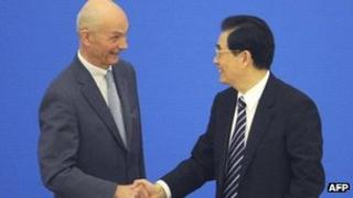 Chinese president Hu Jintao (R) shakes hands with Pascal Lamy (L), the Director General of the WTO at the Great Hall of the People in Beijing, 11 December 2011