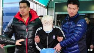A fishing captain suspected of murdering a South Korean coast guard is taken by South Korean maritime police at a hospital in Incheon, west of Seoul, on 12 December 2011