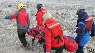 Rescuers carry one of four injured boys to a helicopter in Svalbard