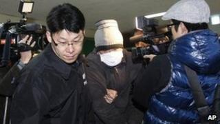 A Chinese fisherman (centre) is led by a South Korean police officer as he arrives at Incheon Coast Guard office in South Korea, 13 December 2011