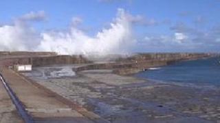 Waves crash over the Alderney breakwater