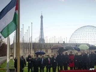 Mahmoud Abbas and other guests look at the Palestinian flag outside Unesco's headquarters in Paris (13 December 2011)