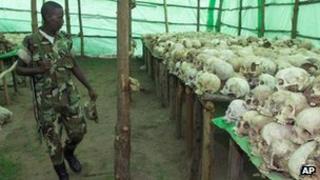 Rwandan soldier looks at the human skulls belonging to victims at the genocide memorial in Bisesero, Rwanda, November 2nd 1999