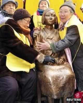 Former South Korean comfort women (wearing yellow vests) pose with the Peace Statue symbolising a wartime sex slave at the 1,000th weekly anti-Japan rally in front of the Japanese embassy in Seoul