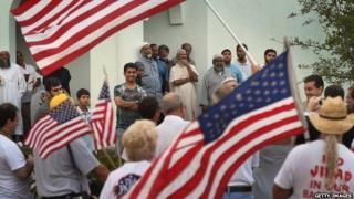 Protesters wave American flags in front of a Florida mosque