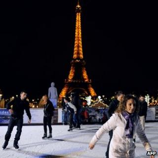 People ice skating in front of the Eiffel tower