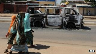 Young girls walk past a burnt-out vehicle in Damaturu, Nigeria (4 Nov 2011)