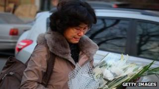 A woman bringing flowers to the North Korean Embassy in Beijing, China to mourn the death of Kim Jong-il.