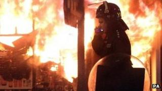 Police officer in front of building set on fire during riots