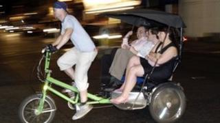 Passengers on a rickshaw in Soho, London