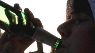 Boy drinking bottle of beer
