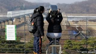 Tourists look across the demilitarised zone into North Korea on 20 December 2011