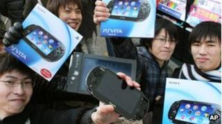 People show off their PlayStation Vita consoles in Tokyo