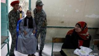 Elderly man helped into polling station at Imbaba in Giza, on the outskirts of Cairo
