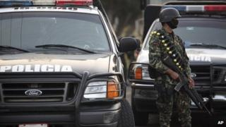 A masked Mexican navy marine keeps custody of police vehicles outside of a police station after the entire police force was disbanded in the Gulf port city of Veracruz, Mexico