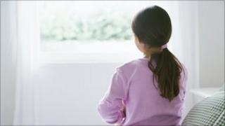 Young female child (girl, youth) sitting alone on the edge of a bed and looking out through a bedroom window
