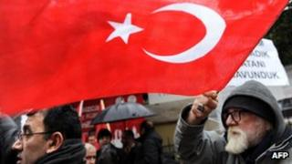 A man waves a Turkish flag as he takes part in a rally in front of the French Consulate in Istanbul