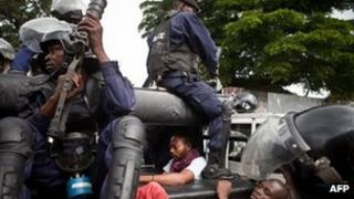 Policemen sit on a truck after they arrested members the Union for Democracy and Social Progress (UDSP) and supporters of opposition leader Etienne Tshisekedi in Kinshasa on 23 December 2011