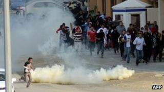 Bahraini anti-government protesters run for cover from tear gas during clashes with riot police near the headquarters of the main Shia opposition group (23 Dec 2011)