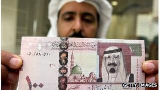 Man holding riyal banknote