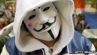 An Occupy protester wears a V for Vendetta mask