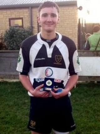 Toby Hearne - wearing rugby kit and holding a trophy