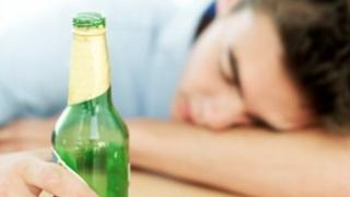 Man holds an empty beer bottle and sleeps