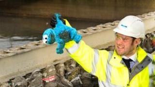 Matt Thompson from Yorkshire Water holds up a cuddly toy in front of a sewer