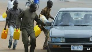 Nigerians try to sell fuel on the black market during a strike in 2004