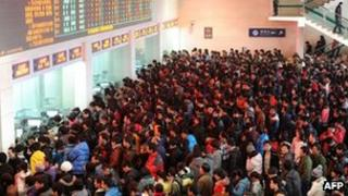 Hundreds of Chinese people queue up to buy train tickets at a railway station in Hefei, east China's Anhui province, 29 December 2011