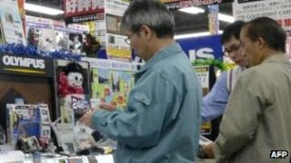 Customers check digital cameras of Japanese optical giant Olympus at a camera shop in Tokyo on December 6, 2011.