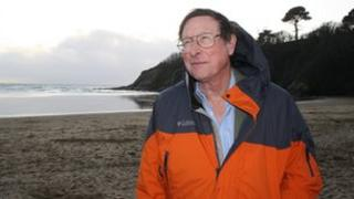 Sir Max Hastings on Porthluney Cove beach by Caerhays Castle