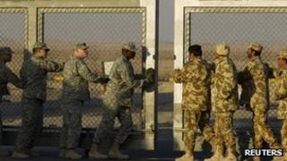 Kuwaiti and US soldiers close the border gate during the US military's withdrawal from Iraq 18 December 2011