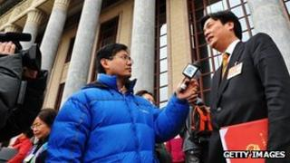 A Chinese TV journalist interviews a delegate outside the Great Hall of the People after closing meeting of the annual National People's Congress (NPC) session in Beijing, 14 March 2011