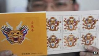 "A man shows stamps featuring a dragon at a post office ahead of the Chinese New Year, or the ear of the Dragon, in Jiaxing, in eastern China""s Zhejiang province Thursday, Jan. 5, 2012."