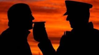 Policeman breathalysing a man
