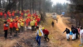 Chilean firefighters look on as police recover the body of a dead colleague