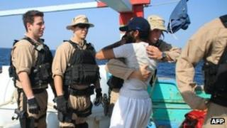 A sailor assigned to the USS Kidd greets a crew member of the Iranian-flagged fishing dhow Al Molai after the US team apparently freed the fishermen from Somali pirates holding them in the Arabian Sea. Image supplied by US Navy